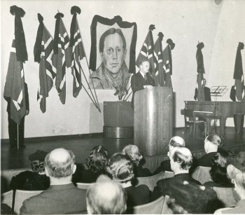 Fra minnefesten for Nordahl Grieg i Medborgarhuset i Stockholm, 9. februar 1944. På talerstolen: forfatter Sigurd Hoel. RA/PA-1209 NTBs krigsarkiv, Uc, 66, 3, S 1022A.
